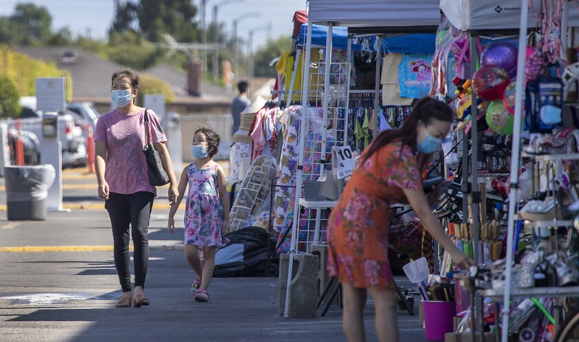 Shoppers in masks walk past stands at an outdoor swap meet