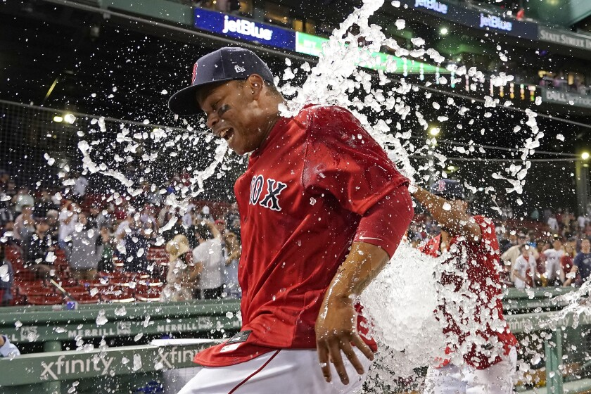 Boston Red Sox's Rafael Devers is doused with ice water to celebrate the team's 6-2 victory over the New York Yankees in a baseball game at Fenway Park, Friday, July 23, 2021, in Boston. Devers hit two home runs in the game. (AP Photo/Elise Amendola)