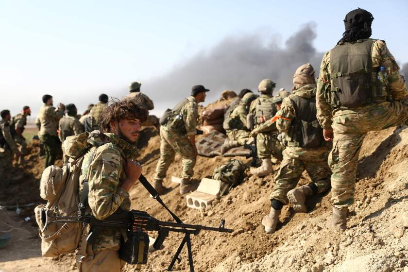 Soldiers watch as smoke billows from the border town of Ras al-Ayn, Syria.