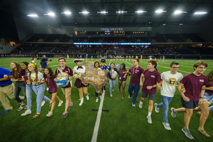 Student government representatives from Plano and El Paso Eastwood high schools lock arms and cross the field.