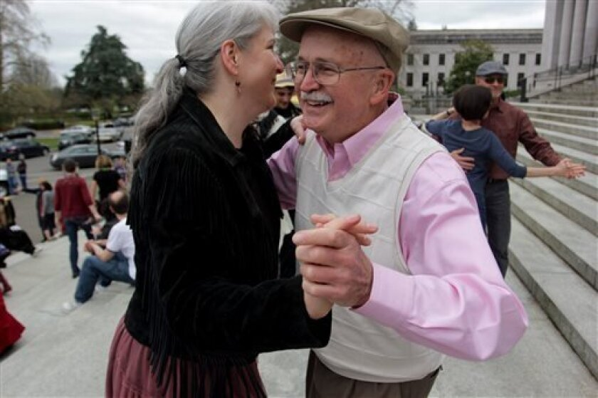 Lauri Miller and Don Morgan dance on the steps of the Capitol in Olympia, Wash., Monday, April 1, 2013. Several dozen people danced in the Washington capital to protest the tax and show support for a measure repealing it. (AP Photo/Manuel Valdes)