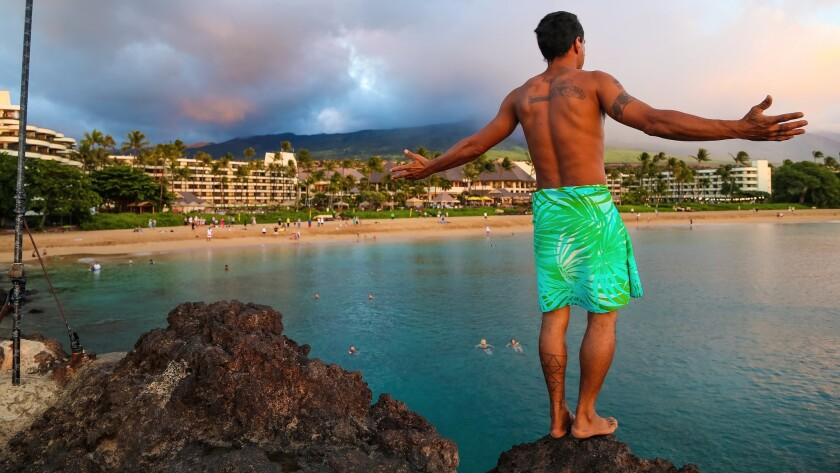 On Maui, a cliff diver jumps 30 feet into the ocean every