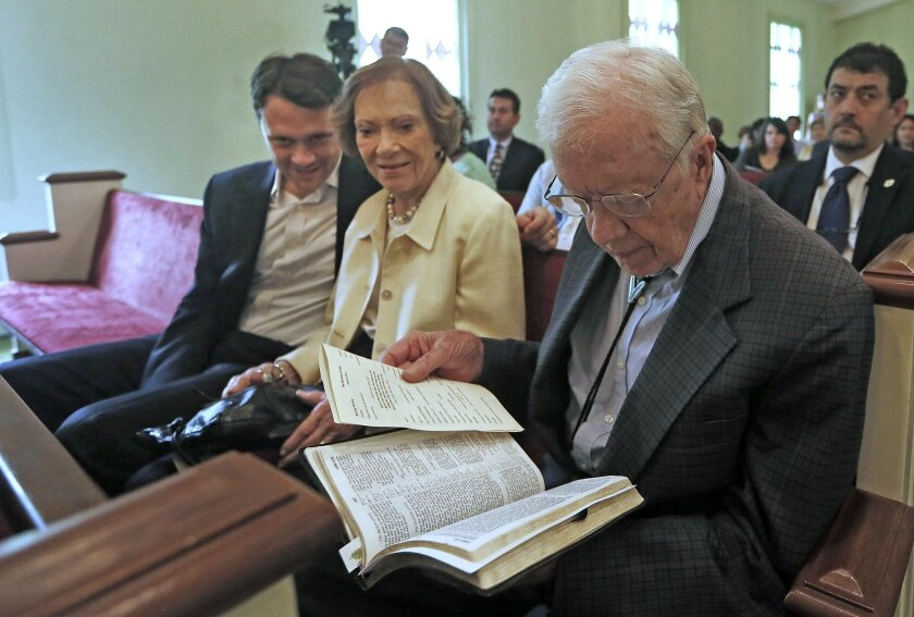 In this photo taken Sunday, June 8, 2014, Georgia Democratic gubernatorial candidate Jason Carter, left, sits with his grandparents Rosalynn and Jimmy Carter during a church service in Plains, Ga. Religion offers a powerful connection with many in the South, and Democrats looking to halt Republican