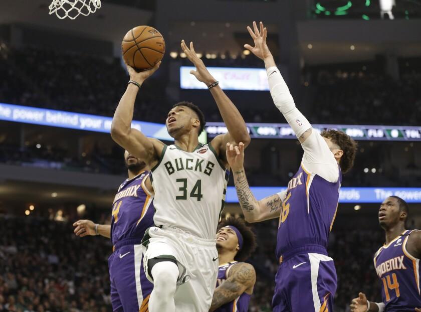 Milwaukee Bucks' Giannis Antetokounmpo (34) shoots against the Phoenix Suns during the first half of an NBA basketball game Sunday, Feb. 2, 2020, in Milwaukee. (AP Photo/Jeffrey Phelps)