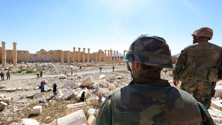 Soldiers look over damage at the historic Bel Temple in the ancient city of Palmyra, Syria, on April 1, 2016.