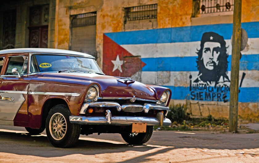 An old Plymouth classic car passes a Cuban flag and Che Guevara mural painted on an eroded wall in Old Havana.