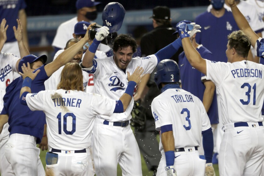 The Dodgers' Cody Bellinger is welcomed by teammates after his walk-off home run against the Colorado Rockies