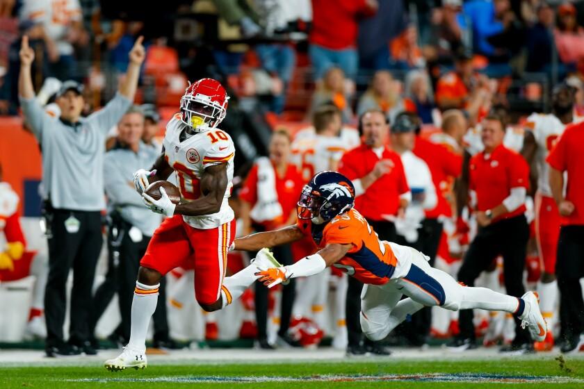 Kansas City wide receiver Tyreek Hill catches a touchdown pass ahead of Denver Broncos cornerback Chris Harris Jr.