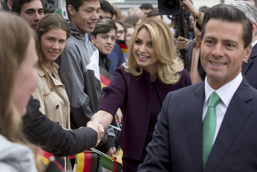 FILE - In this April 11, 2016 file photo, Mexico's President Enrique Pena Nieto, right, and his wife Angelica Rivera de Pena greet students as they arrive to meet with Germany's President Joachim Gauck at Bellevue Palace in Berlin, Germany.  Pena Nieto apologized on Monday, July 18, 2016 for a 2014