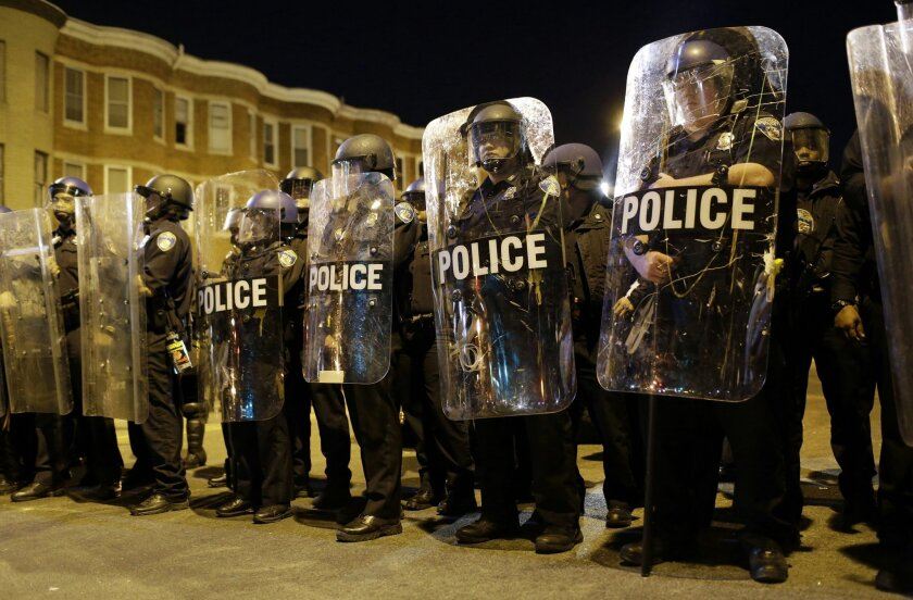 FILE - In this April 28, 2015 file photo, police stand in formation as a curfew approache in Baltimore, a day after unrest that occurred following Freddie Gray's funeral. The prevailing images of protests in Baltimore and Ferguson, Missouri, over police killings of black men were of police in riot gear, handcuffed protesters, tear gas and mass arrests. The main images of a fatal gun battle between armed bikers and police in Waco, Texas, also showed mass arrests _ carried out by nonchalant-looking officers sitting around calm bikers on cell phones. (AP Photo/Patrick Semansky, File)