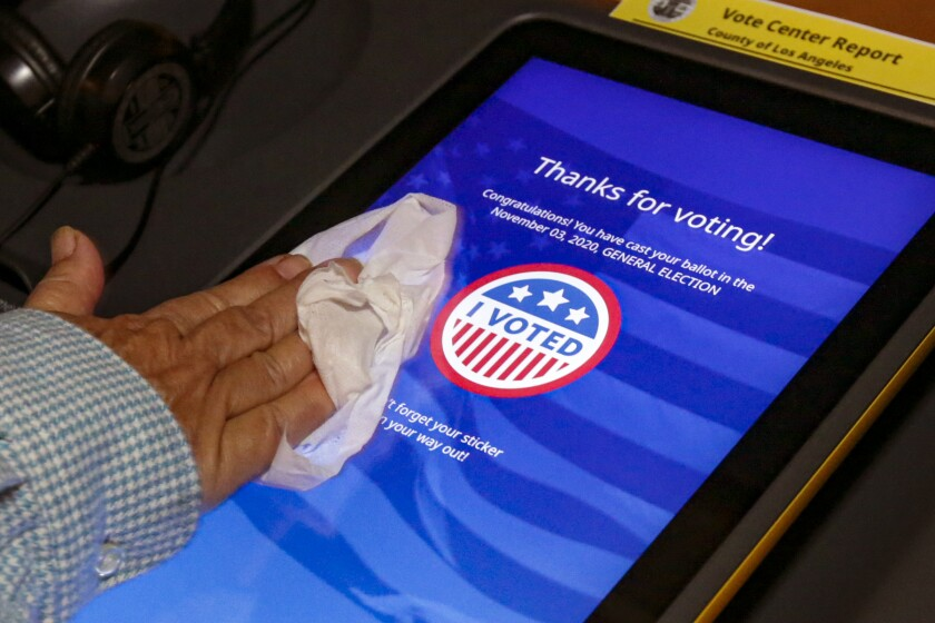 Clerk Cristina Madrid sanitizes polling booths after every use at an in-person early voting place at Azusa Women's Club.