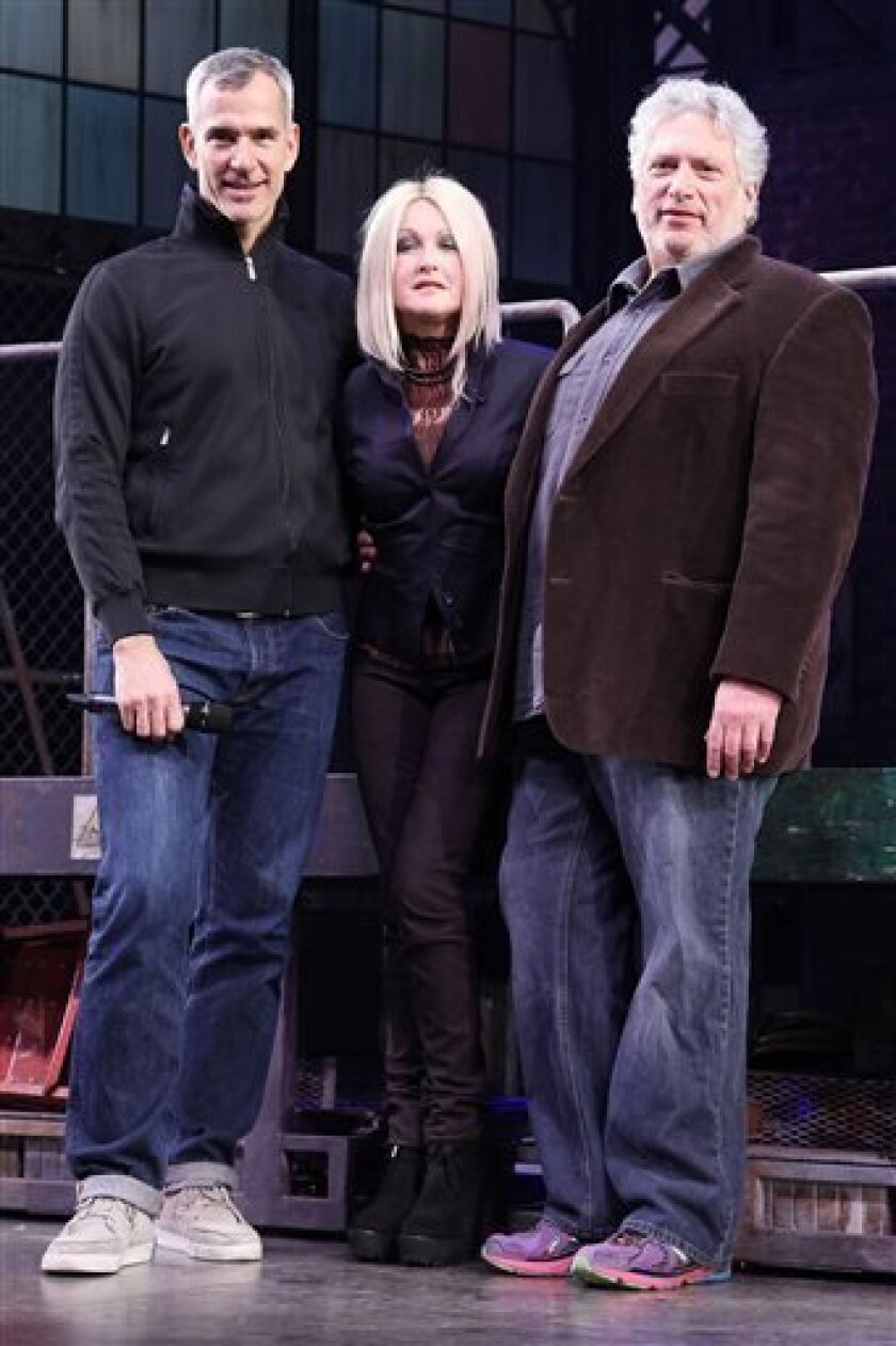 """FILE - This Feb. 28, 2013 photo released by Starpix shows, from left, choreographer Jerry Mitchell, Cyndi Lauper and Harvey Fierstein at the open house for the Upcoming Musical """"Kinky Boots,"""" at the Al Hirshfeld Theatre in New York.  The Cyndi Lauper-scored """"Kinky Boots"""" has earned a leading 13 Ton"""