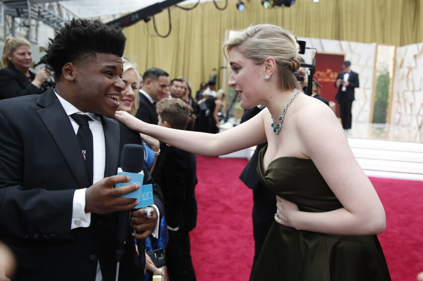 Greta Gerwig talks with Jerry Harris on the red carpet at the Oscars.
