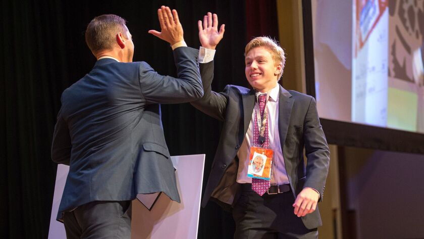 John Dumoulin, 17, of Virginia gets a high-five from Aaron Osmond, general manager at Certiport, aft
