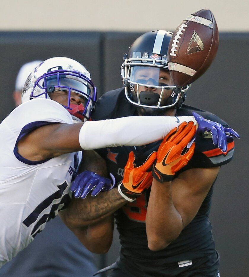 TCU safety Nick Orr (18) breaks up a pass intended for Oklahoma State wide receiver Marcell Ateman, right, in the second quarter of an NCAA college football game in Stillwater, Okla., Saturday, Nov. 7, 2015. (AP Photo/Sue Ogrocki)