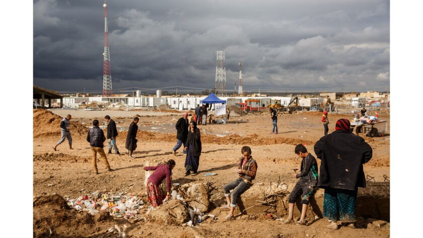 People linger outside as the rain pauses, at a United Nations displaced persons camp in Hammam Alil, Iraq on 16