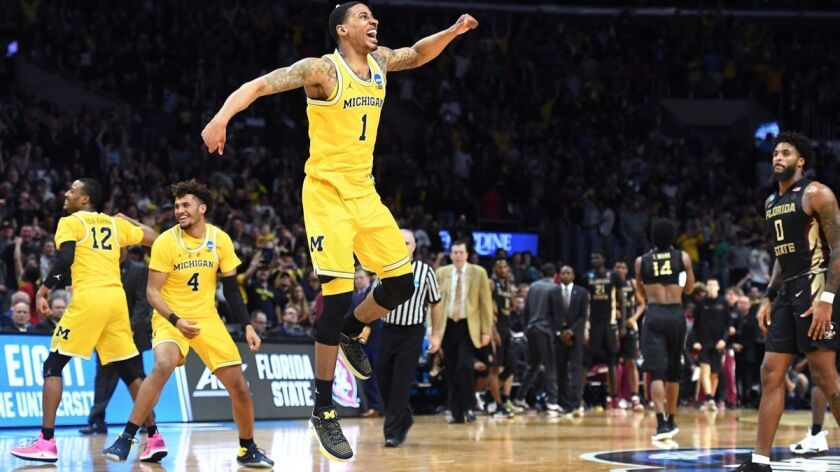 Michigan's Charles Matthews, center, celebrates at the end of the game to defeat Florida State in the regional final of the NCAA tournament at the Staples Center Saturday.