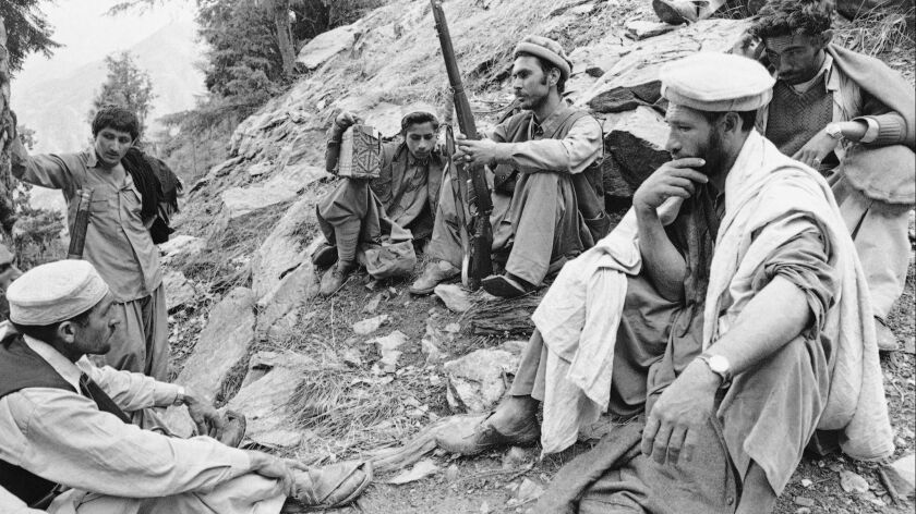 A group of Afghan mujahedeen listens to the radio as they take a rest in the rocky mountainous area