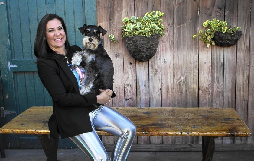 Carrie Cramer, the owner of Carrie Cramer Jewelry, with her dog Atticus, a 5-year-old schnauzer.