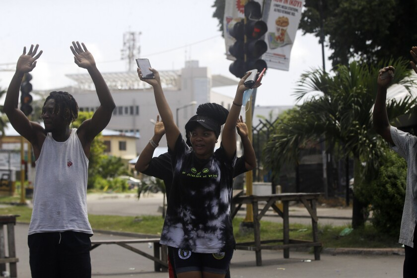 People rise their hands as they approach a police check point in Lagos, Nigeria, Thursday Oct. 22, 2020. Lagos streets were empty and shops were shuttered Thursday, as residents of Nigeria's largest city obeyed the government's curfew, stopping the protests against police brutality that had lasted for two weeks. ( AP Photo/Sunday Alamba)