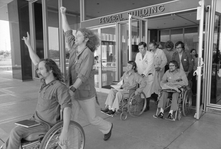 Ron Kovic, left, leads disabled veterans from the Wilshire Boulevard federal building afer ending a 17 day hunger strike.