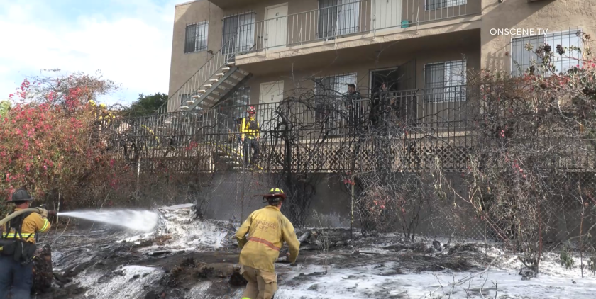 A three-story apartment complex in San Ysidro was briefly threatened by a brush fire early Monday.