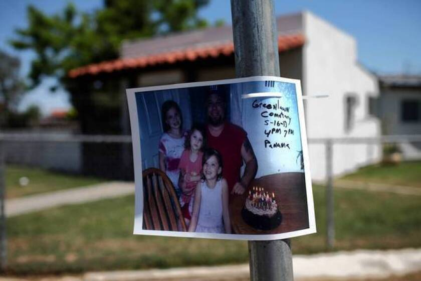 A photo of David Sal Silva and his children is posted on a pole at Flower and Palm streets in Bakersfield, where he was beaten by sheriff's deputies.