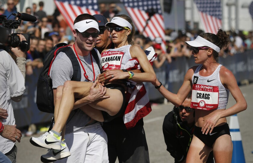 Steve Edwards carries his wife, Shalane Flanagan, after she fell to the ground in exhaustion following her third-place finish in the U.S. Olympic women's marathon trial on Saturday. Training partner Amy Cragg, who won the race, was the first to arrive at her side as Flanagan crossed the finish line.