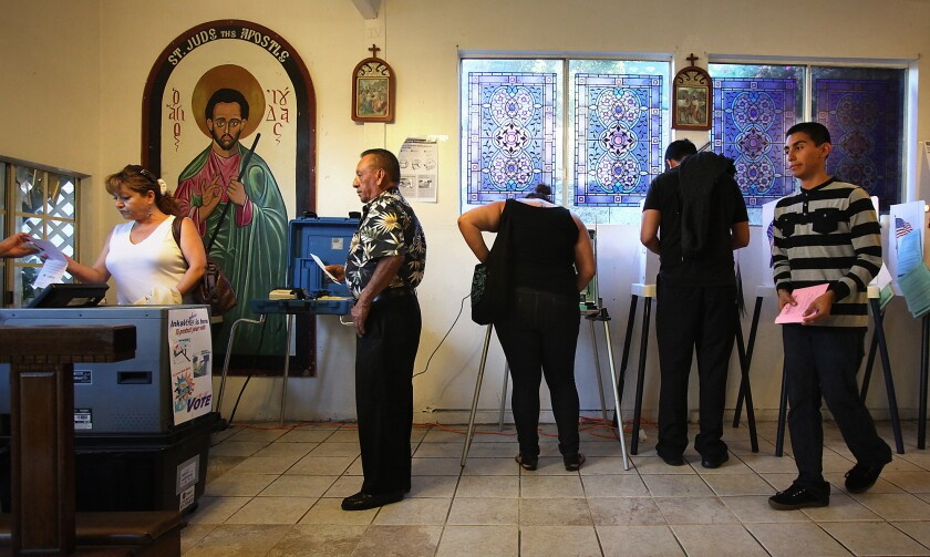 Voters make their way in and out of a polling place at the House of Mercy in Los Angeles in November 2012.