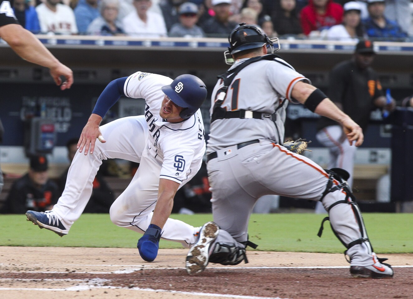 The Padres' Hunter Renfroe is tagged out at home plate by Giants' catcher Stephen Vogt as he tries to score on a single hit by Greg Garcia in the third inning at Petco Park on Wednesday, July 3, 2019 in San Diego, California.