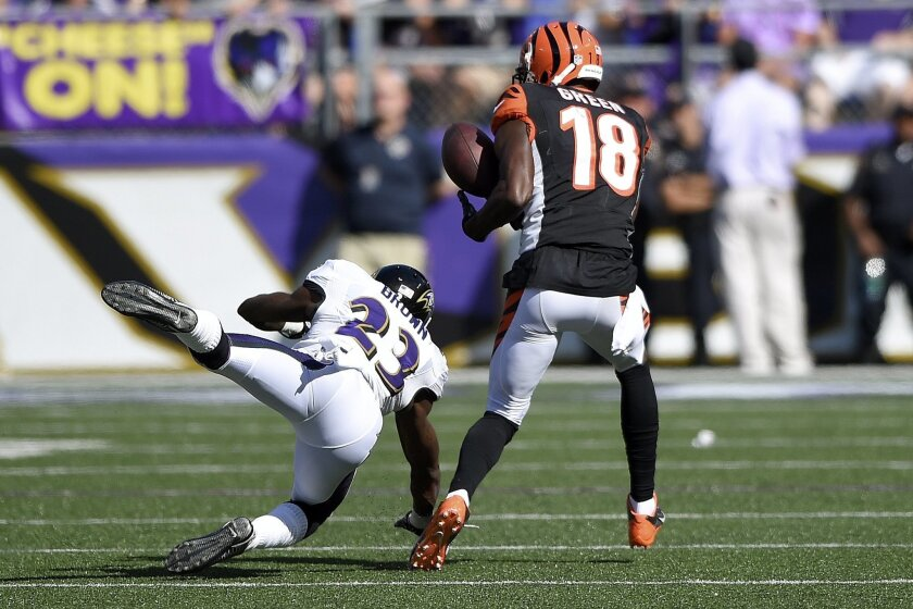 Cincinnati Bengals wide receiver A.J. Green (18) catches a 77-yard touchdown pass under pressure from Baltimore Ravens defensive back Chykie Brown (23) during the second half of an NFL football game in Baltimore, Md., Sunday, Sept. 7, 2014. The Bengals defeated the Ravens 23-16. (AP Photo/Nick Wass)