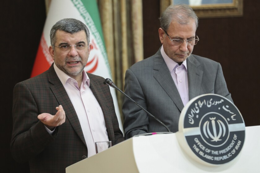 FILE — In this Feb. 24, 2020 file photo, released by the official website of the office of the Iranian Presidency, the head of Iran's counter-coronavirus task force, Iraj Harirchi, left, speaks at a press briefing with government spokesman Ali Rabiei, in Tehran, Iran. Appearing before the cameras, sweating profusely and coughing, Harirchi, the man leading Iran's response to the new coronavirus promised it was of no danger to his country. A day later, he himself would be in quarantine from the virus. For most people, the new coronavirus causes only mild or moderate symptoms. For some it can cause more severe illness. (Iranian Presidency Office via AP, File)