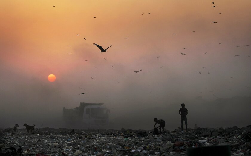 FILE- In this Oct. 17, 2014, file photo, a thick blanket of smoke is seen against the setting sun as young ragpickers search for reusable material at a garbage dump in New Delhi, India. India's filthy air is cutting 660 million lives short by about three years, while nearly all of the country's 1.2 billion citizens are breathing in harmful pollution levels, according to research published Saturday, Feb. 21. While New Delhi last year earned the dubious title of being the world's most polluted city, the problem extends nationwide, with 13 Indian cities now on the World Health Organization's list of the 20 most polluted. (AP Photo/Altaf Qadri, File)