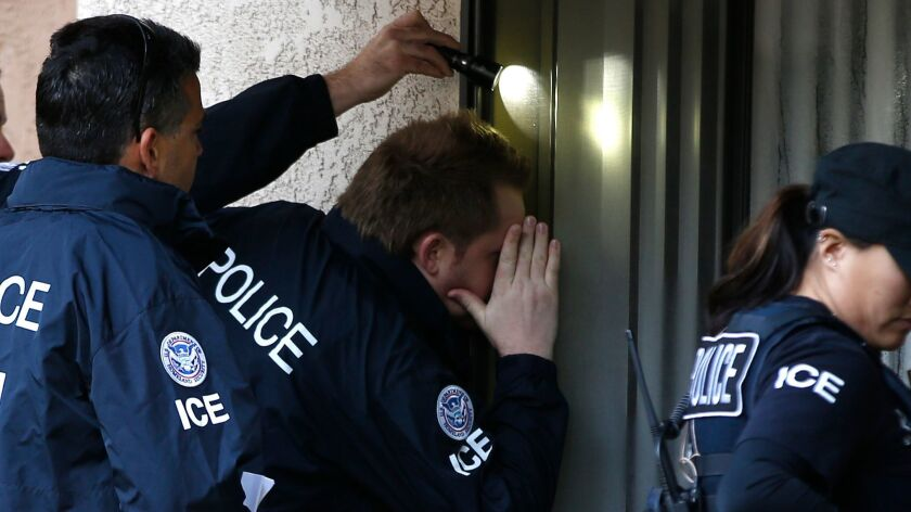 ICE Agents look into the window of an apartment in Rowland Heights while executing search warrants during the ongoing investigatiion into alleged birth tourism centers in March 2015.