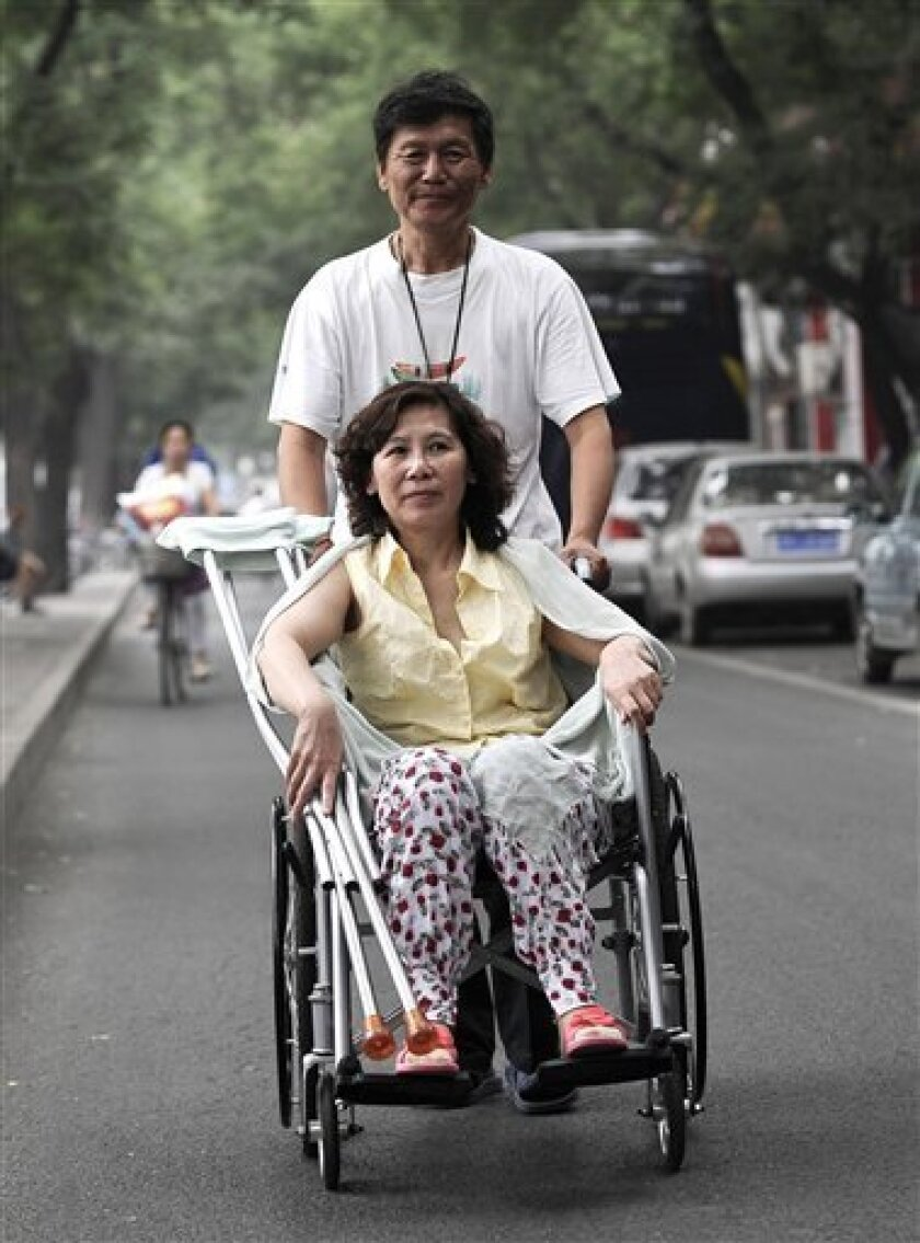 FILE - In this June 30, 2010 file photo, Ni Yulan is helped by her husband Dong Jiqin while heading back to a hotel in Beijing. Ni, a veteran Chinese activist left disabled by past police mistreatment was sentenced Tuesday, April 10, 2012, to two years and eight months in jail for fraud and provoking trouble. Ni was sentenced by a Beijing court with her husband, Dong, who was jailed for two years. (AP Photo/Andy Wong, File)