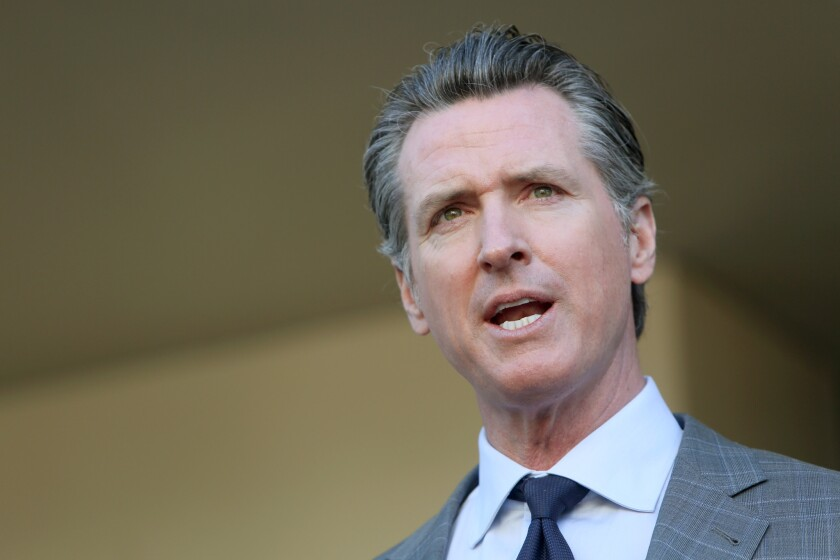 Gov. Gavin Newsom speaks to members of the press after a meeting.
