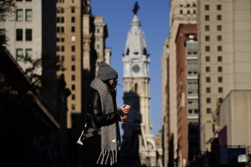 Una persona con mascarilla cruzando la calle Broad en Filadelfia.