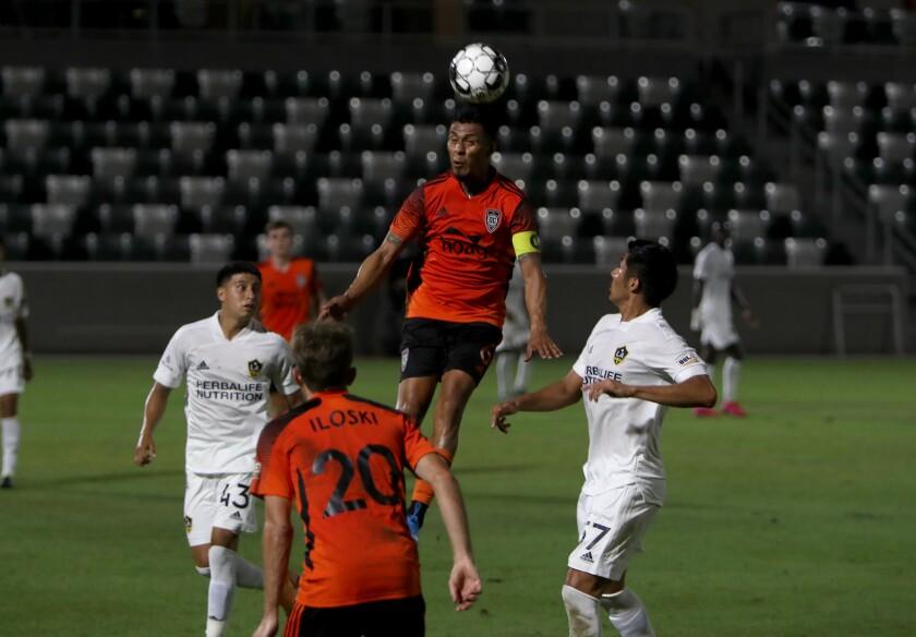 El defensor del Orange County Soccer Club, Michael Orozco, cabecea el balón contra LA Galaxy II.