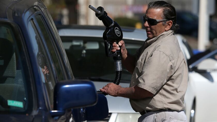A customer prepares to pump gasoline into his car at an Arco gas station in Mill Valley, Calif. State lawmakers are considering a new tax on oil pumped from the ground, which could affect gas prices.