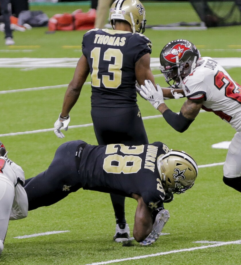New Orleans Saints running back Latavius Murray (28) lands on wide receiver Michael Thomas' right ankle while being tackled by Tampa Bay Buccaneers safety Antoine Winfield Jr., left, late in the fourth quarter of an NFL football game in New Orleans, Sunday, Sept. 13, 2020. (Andrew Stagni/The Advocate via AP)