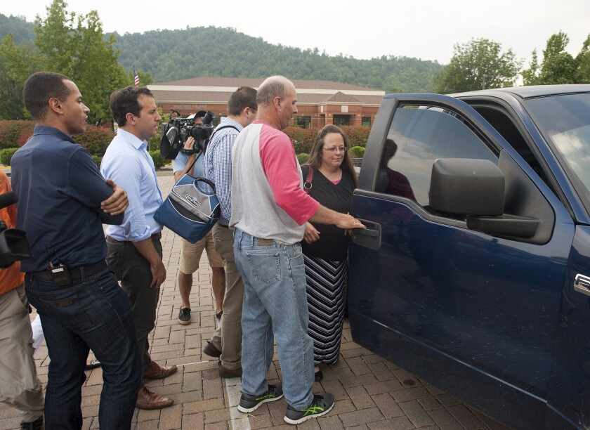 Members of the media follow Rowan County, Ky., Clerk Kim Davis as she is escorted to her vehicle at the Rowan County Courthouse in Morehead, Ky.