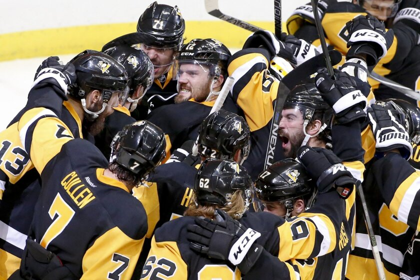 Pittsburgh Penguins celebrate as they gather around goalie Matt Murray after defeating the Tampa Bay Lightning 2-1 in Game 7 of the NHL hockey Stanley Cup Eastern Conference finals, Thursday, May 26, 2016, in Pittsburgh to advance to the Stanley Cup finals. (AP Photo/Gene J. Puskar)