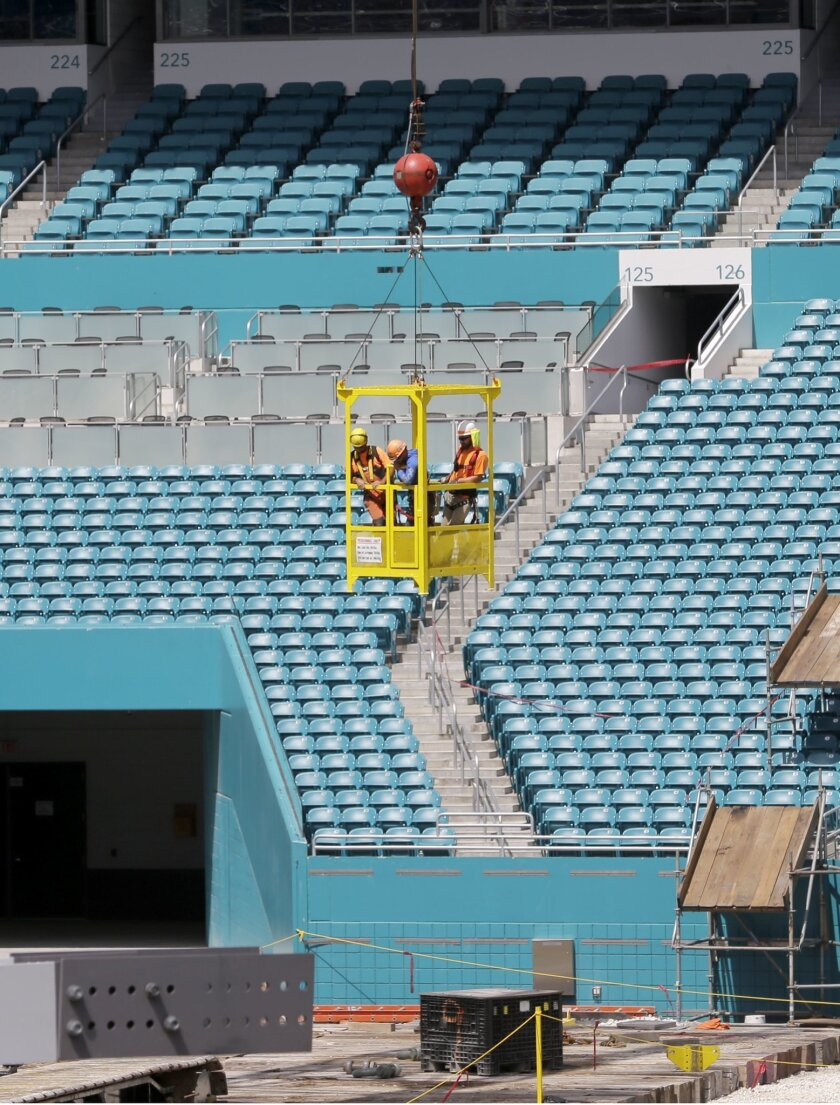 Three construction workers are lowered to the field by a crane at the Miami Dolphins' NFL football stadium, Thursday, June 2, 2016, in Miami Gardens, Fla. The first game of 2016 is three months away, and the stadium is far from ready. But Dolphins officials say they're on schedule with a major reno
