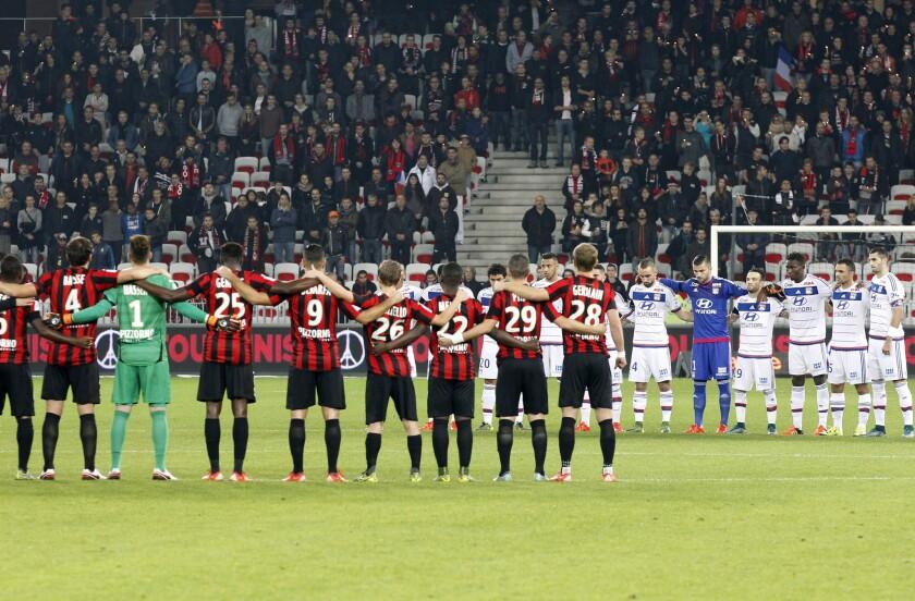 Jugadores del Niza (i), y Lyon guardan un minuto de silencio previo a un partido de la liga francesa en Niza.