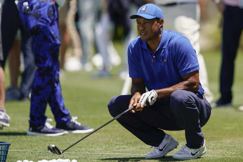 Tiger Woods crouches at the driving range during a practice day for the U.S. Open Championship golf