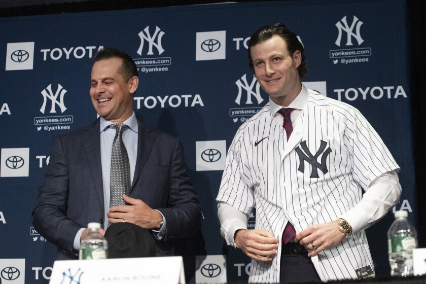"""FILE - In this Dec. 18, 2019, file photo, New York Yankees manager Aaron Boone, left, smiles as Gerrit Cole tries on a Yankee jersey as he is introduced in New York. The pitcher agreed to a 9-year $324 million contract. """"He's going to be a game changer for us,"""" Yankees owner Hal Steinbrenner said. """"The city's buzzing, and it's continued since the day we signed him."""" (AP Photo/Mark Lennihan, File)"""
