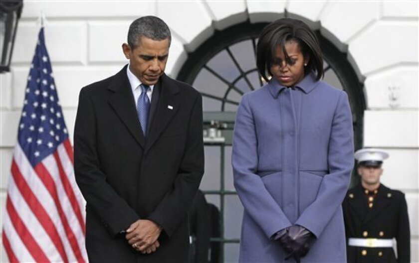 President Barack Obama and first lady Michelle Obama are joined by government employees on the South Lawn of the White House in Washington, Monday, Jan. 10, 2011, to observe a moment of silence for Rep. Gabrielle Giffords, D-Ariz., and the other victims of an assassination attempt against her. The shooting at a town hall-style event outside a supermarket in Tucson, Ariz., Saturday left six dead, including a federal judge, and critically wounded Rep. Gabrielle Giffords. (AP Photo/J. Scott Applewhite)