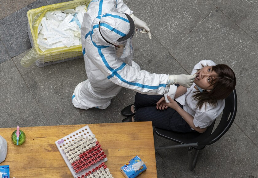 A Wuhan resident is tested for the coronavirus. The new infections reported May 10 were the first since early April.