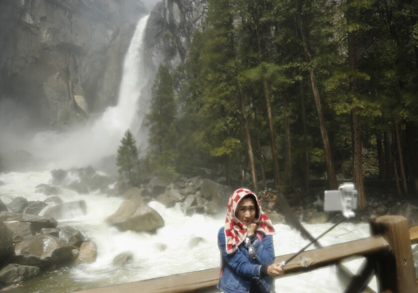 A woman takes a selfie at Lower Yosemite Falls. Would you still go to a destination if you weren't allowed to take a photo?
