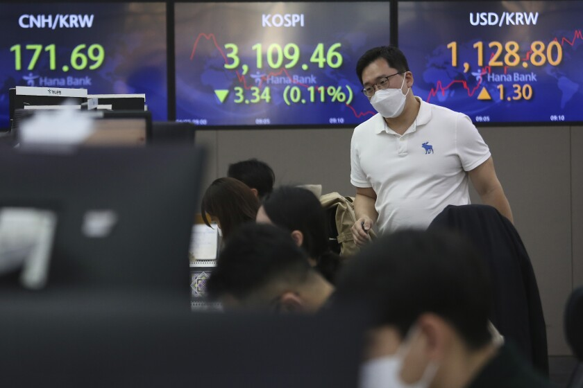 A currency trader passes by screens showing the Korea Composite Stock Price Index (KOSPI), center, and the foreign exchange rate between U.S. dollar and South Korean won, right, at the foreign exchange dealing room of the KEB Hana Bank headquarters in Seoul, South Korea, Monday, April 5, 2021. Asian stock markets were mostly higher Monday after Wall Street hit a record high on optimism the spread of coronavirus vaccines might allow global business to return to normal. (AP Photo/Ahn Young-joon)
